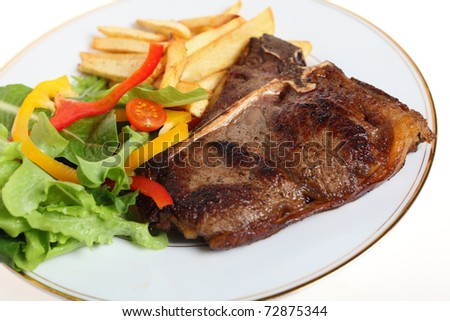 A T-bone steak, pan-seared and served with salad and fries.