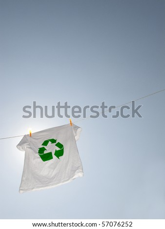 A t-shirt with the recycling symbol hanging on a clothesline - stock photo