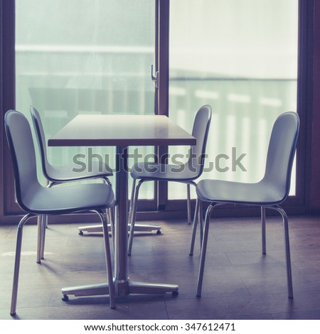 A table and four chairs by French windows. Toned image.
