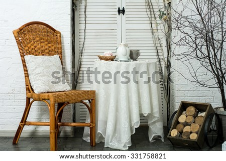A table covered with thick cloth with a cup of tea and coffee on the background of the door. Tea Party. Design veranda with a chair with a pillow and firewood - stock photo