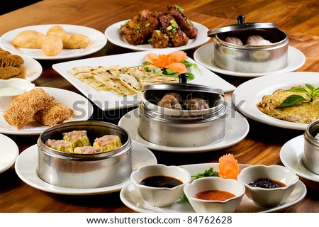 A table filled with plates of Chinese Dim Sum dumplings, cake, sticky rice and other delicious food. - stock photo