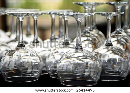A table full of water and wine glasses under lights for a catered event, reception, and/or party (shallow focus point on foreground glasses). - stock photo