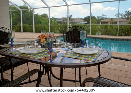 a table is set for dinner on an outside patio or lanai with swimming pool in background, the patio is screened in. - stock photo