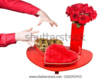 A table is set up with a red vase with red roses beside an open heart shaped box of chocolates.  A mans hands are shown about to grab the chocolates.  Isolated on white.  - stock photo