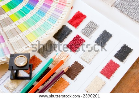 A table of a color muster with pencil and magnifying glass on a colorfull pattern stoff for decoration and design planning - stock photo