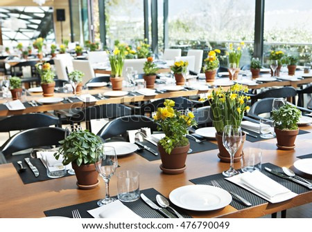 a table of a restaurant with beautiful decoration vases with flowers on a blurry background