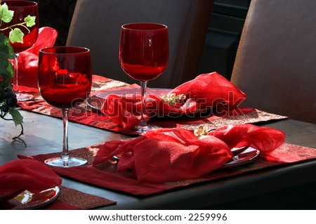 A table place setting of ruby red stemware, plates and linens