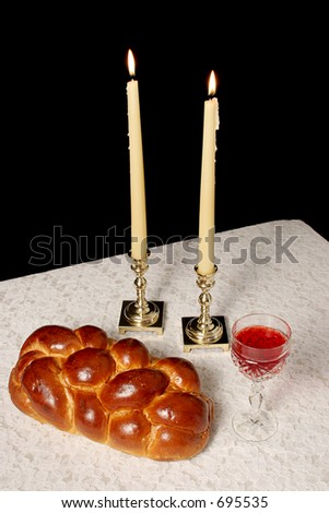 A table set for Shabbat with lighted candles, challah bread and wine. Vertical view with black background. - stock photo