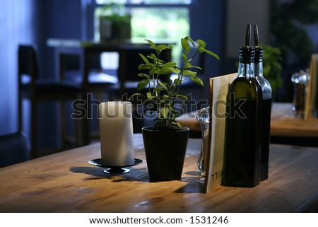 A table setting in a restaurant consisting of bottles of olive oil and vinegar with a pot of mint on wooden table - stock photo