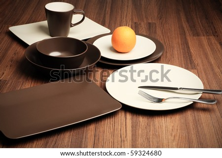 A table setting with different plates, mug, fork and knife. - stock photo