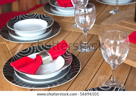 a table setting with red napkin and patterned plates - stock photo