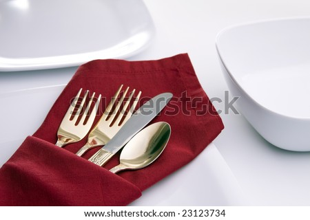A table setting with white plates and bowl, a red napkin folded into a silverware pouch and gold silverware. - stock photo