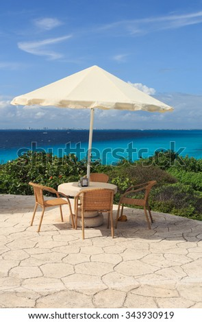 A table with an umbrella on the Caribbean coast - stock photo