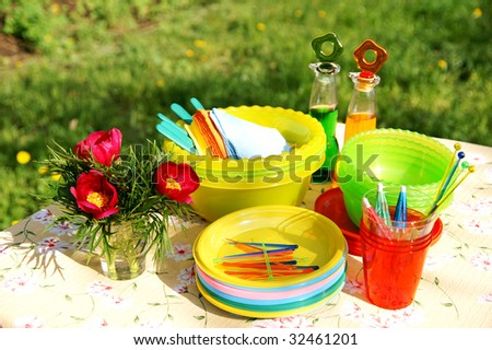A table with bright multicolor summer picnic plastic accessories, plates and dishes, napkins, bottles and flowers - stock photo