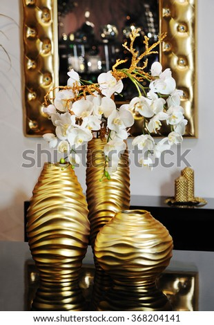 a table with bronze vases and a bronze mirror in the background on a classic home decoration style