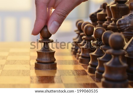 A table with chess standing in two rows and a hand moving a pawn