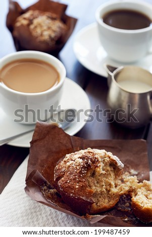 A table with cups of coffee and muffins on it - stock photo