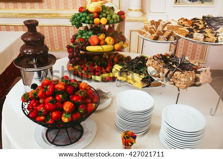 A table with hot chocolate, fruits and pastry - stock photo