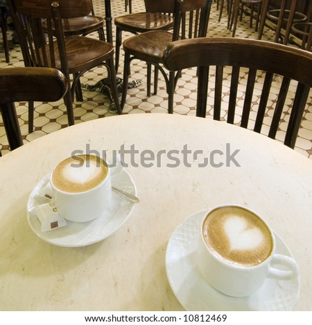 A table with two coffees with two harts
