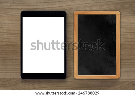 A tablet computer and a vintage chalkboard on a wooden desktop - stock photo