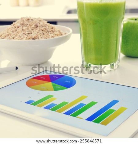 a tablet computer showing some charts and a bowl with cereals, a glass with a green smoothie and an apple on the kitchen table - stock photo