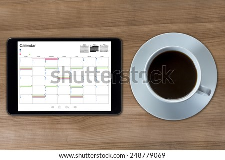 A tablet computer with a calendar displayed and a cup of coffee on a wooden desktop - stock photo