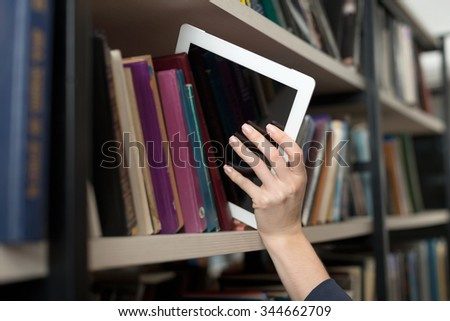 a tablet picked with a hand from a book shelf in the library, a concept of learning and choice - stock photo