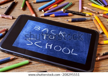 a tablet with a picture of a chalkboard with the sentence back to school written in it, on a rustic wooden desk with worn pencil crayons of different colors - stock photo