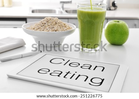 a tablet with the text clean eating written in it and a bowl with oatmeal cereal, a glass with a green smoothie and an apple on the kitchen table - stock photo