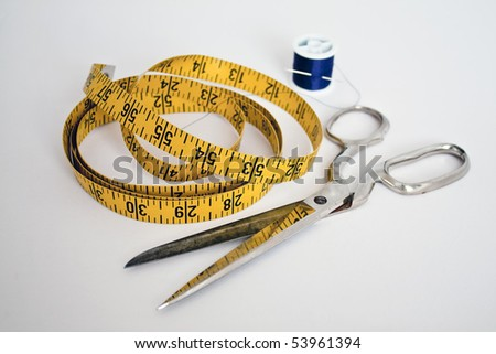 a tailor's tools:  scissors, needle and thread, and a yellow measuring tape - all on an isolated white background - stock photo