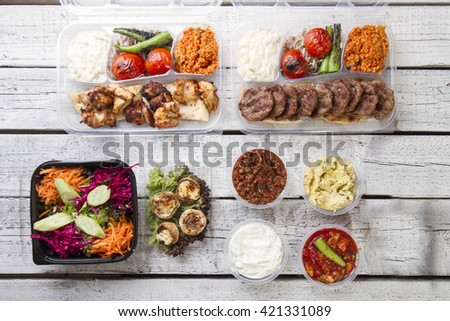 A take away plate with gyros meat and salad on top view white wood background - stock photo