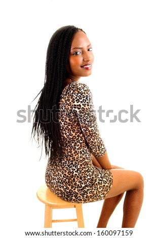 A tall black woman in a brown short dress sitting on a chair with her long braided hair for white background.  - stock photo