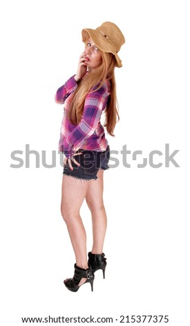 A tall blond woman standing in shorts, wearing a straw hat,  isolated over white background.  - stock photo
