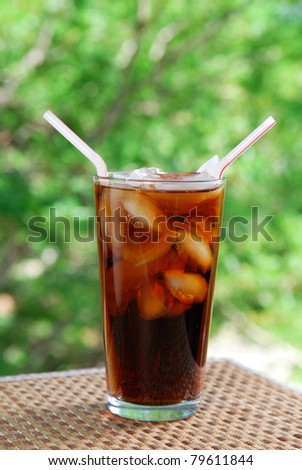 A tall cola with two straws served on the terrace - stock photo