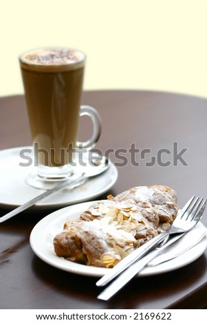 A tall glass of hot capucinno with a delicious crispy almond croissant on a wooden table, against white with copyspace. - stock photo