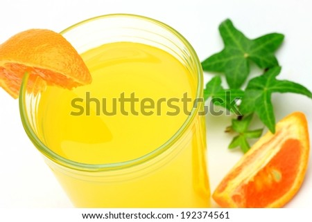 A tall glass of orange juice with a slice of orange on the rim. - stock photo
