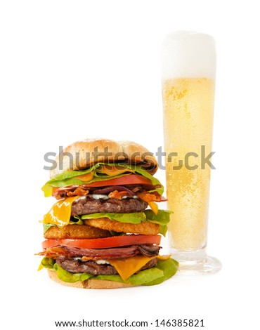 A tall hamburger stacked with two beef patties, crisp bacon, cheddar cheese, blue cheese, grilled onions, tomato, lettuce and special sauce. Served with a tall glass of cold beer with a head of foam.