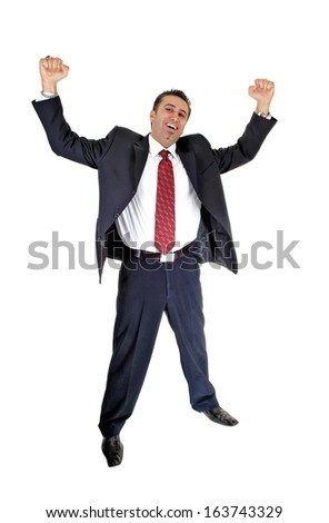 A tall handsome businessman standing for white background in a blue  suit and red tie lifting up his arms for happiness.