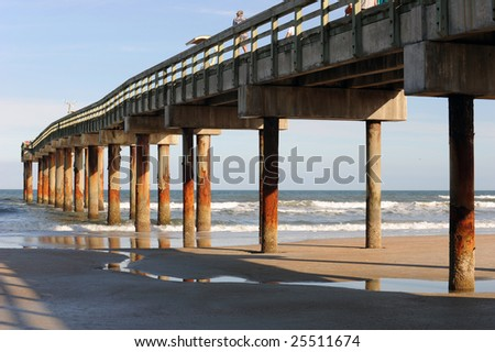 A tall pier taken in the late afternoon sunlight showing long, deep shadows. - stock photo