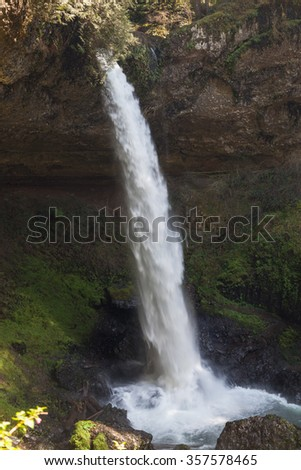 A tall powerful waterfall in Silver Falls State Park in Oregon flows over a shelf of rock and down a deep canyon. - stock photo
