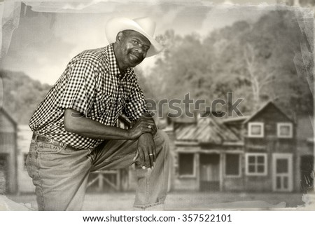 A tall, senior black cowboy in an old western town.   - stock photo