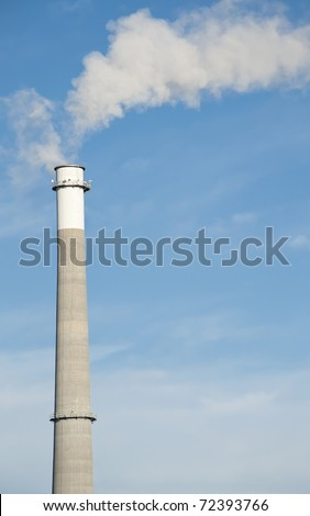 A Tall Smoke Stack Releasing Pollution into the Sky - stock photo