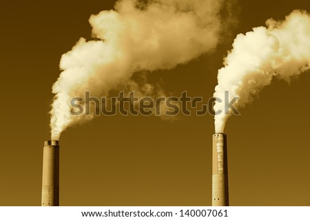 A tall smokestack spewing out dirty polluted smoke - stock photo