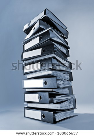 A tall stack of ring binders. - stock photo
