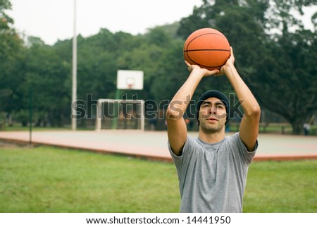 A tall standing man, preparing to shoot a basketball in a park, concentrating - horizontally framed - stock photo