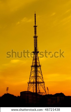 a tall telecommunication tower during  a tropical sunset - stock photo
