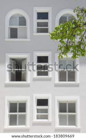 A tall white building with windows of various shapes and sizes. - stock photo