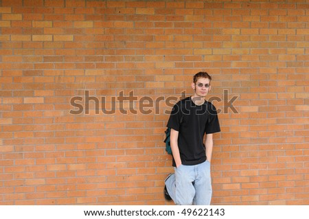 A tall white Caucasian young adult teenage male stands in front of a brick wall. Lots of room for your copyspace text. He has a backpack and glasses - stock photo