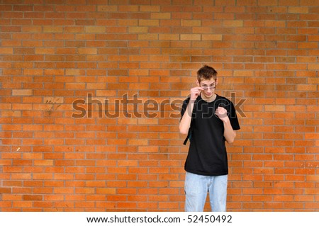 A tall white Caucasian young adult teenage male stands in front of a brick wall pulling down his glasses. Lots of room for your copyspace text. He his wearing a backpack - stock photo
