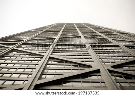 A tall windowed building viewed from a low angle. - stock photo